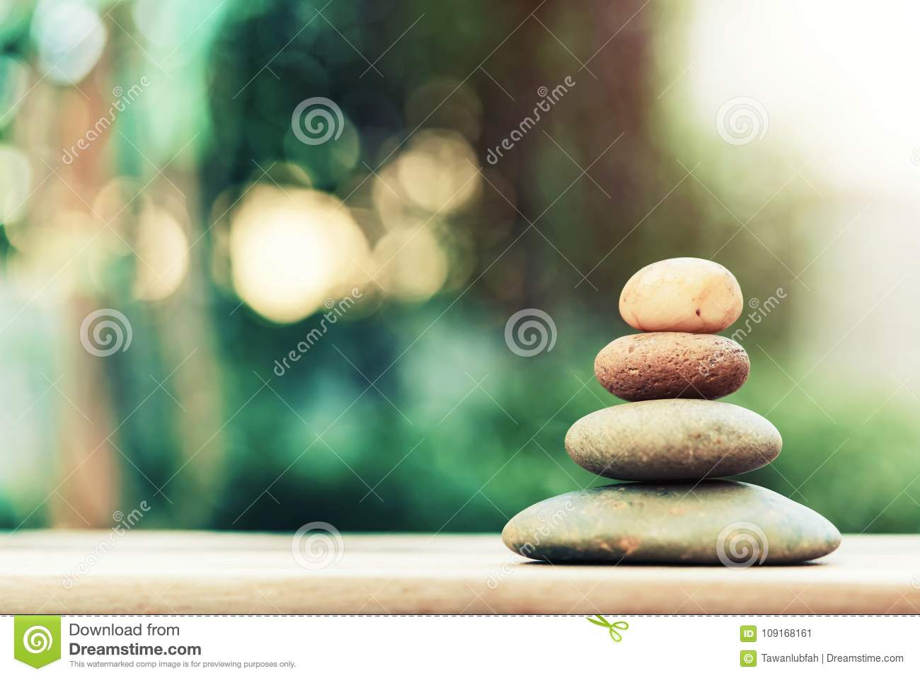 Stack of zen stones on ground with blurred nature background.