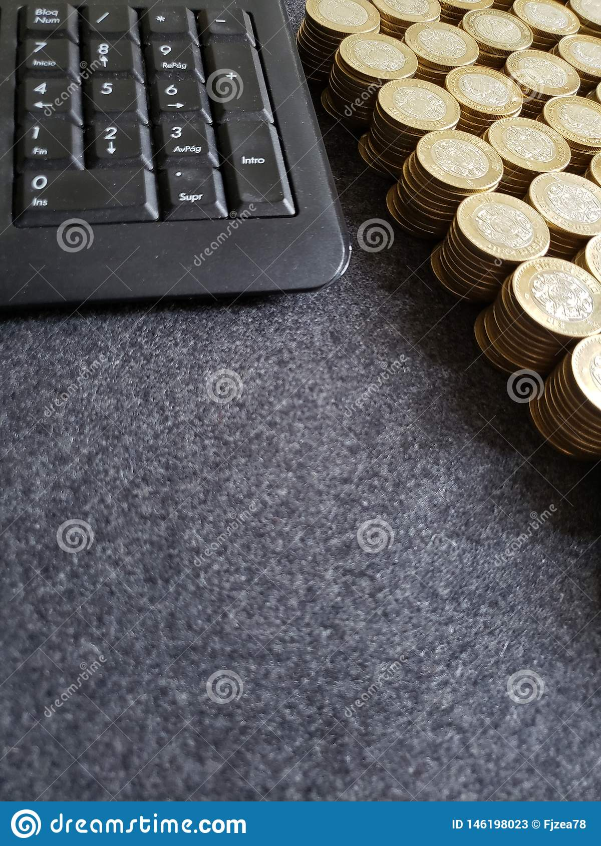 stacked coins of ten mexican pesos and computer numeric keypad