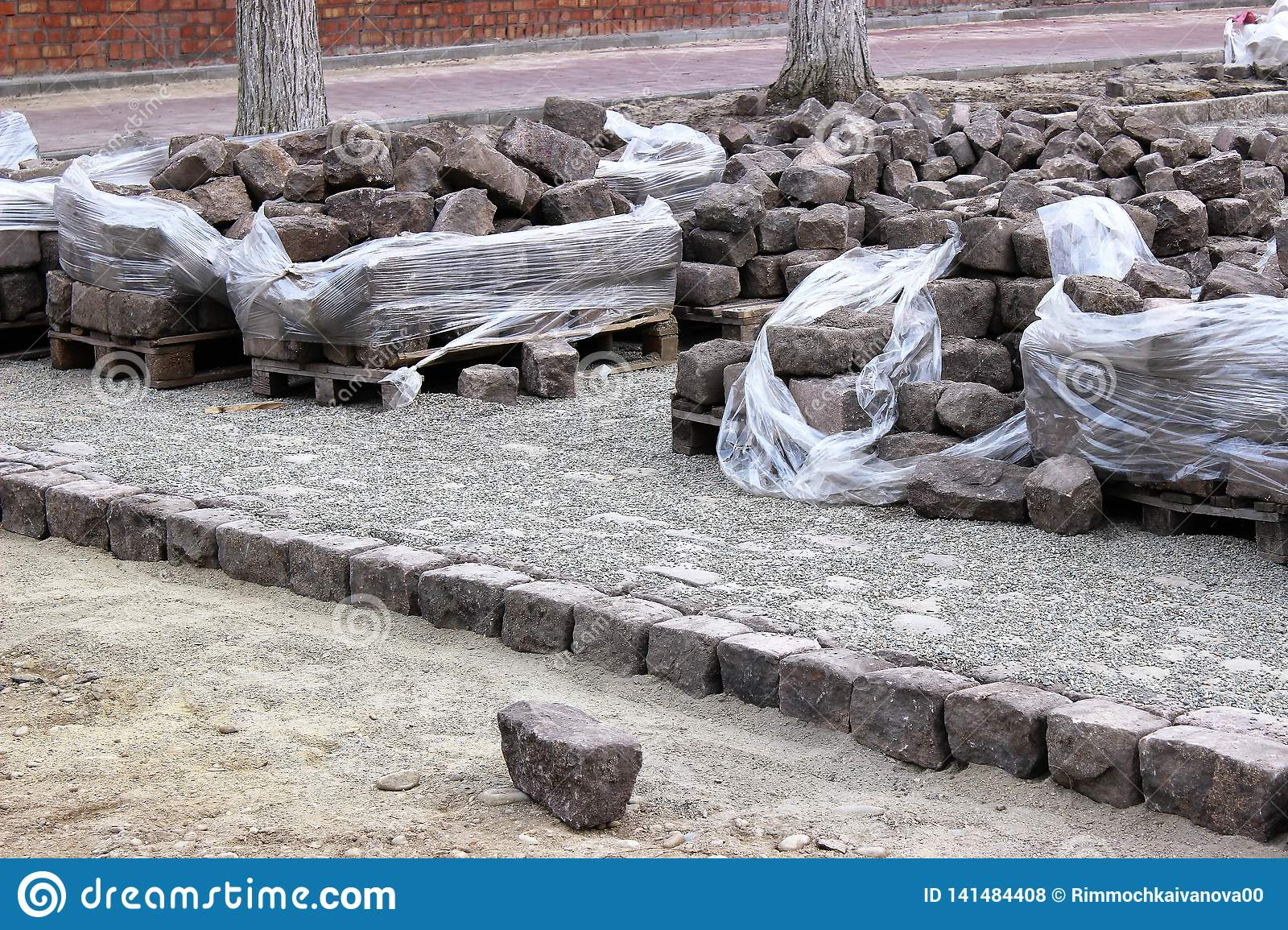 Stacks of old cobblestones lie along the street, which is being renovated