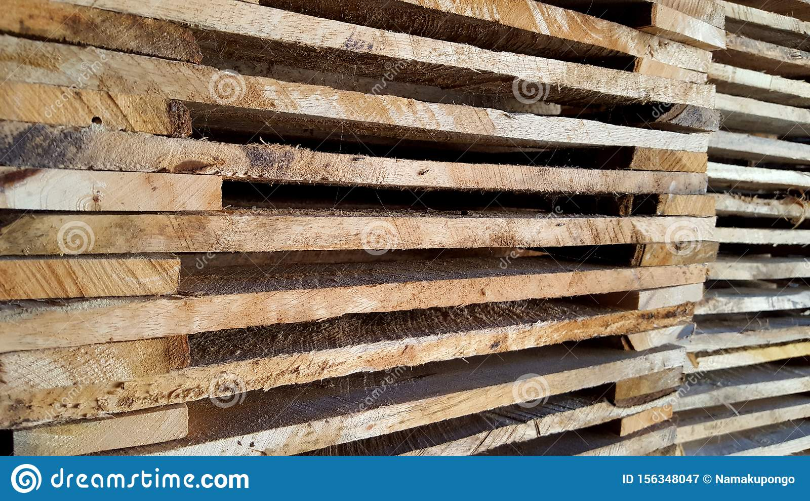 Stacks of wooden pallets, neatly lined up ready to use