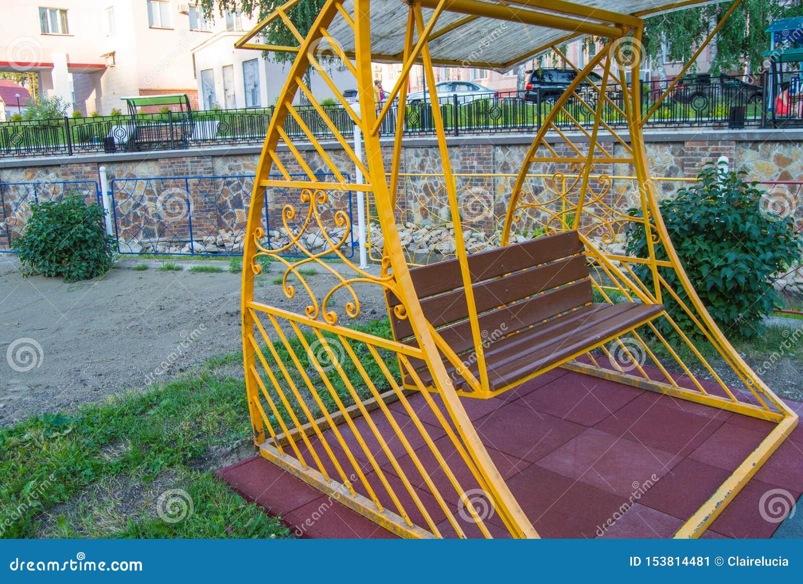 Staden parkerar i sommar, tom trägunga med den gula dekorativa metallramen, utomhus- fritidmöblemang