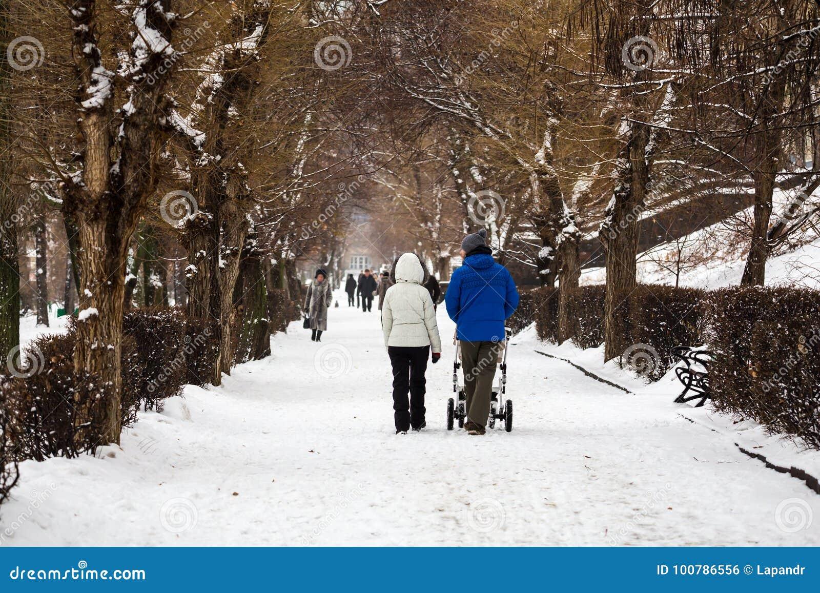 Staden parkerar i vinter En ung familj går Mamma, farsa och en sittvagn med ett småbarn