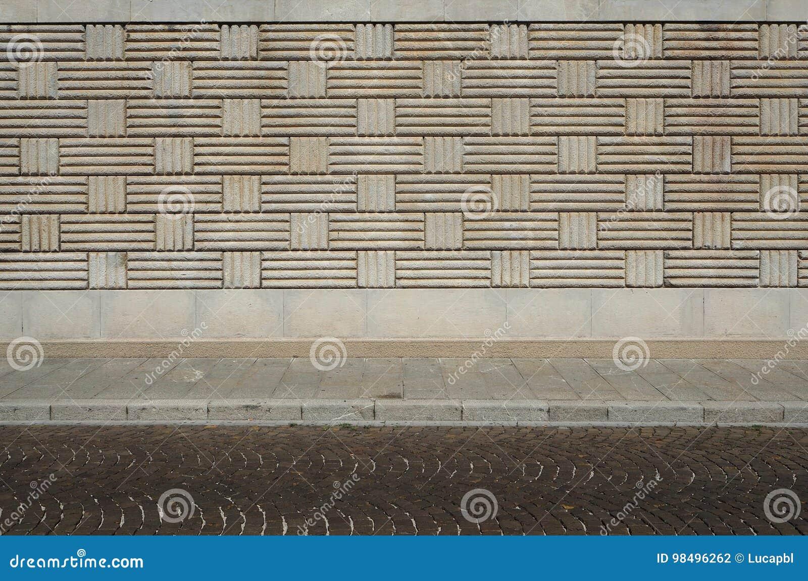 Stads- bakgrund Vägg med den geometriska modeller, trottoaren och gatan med porfyrkuber