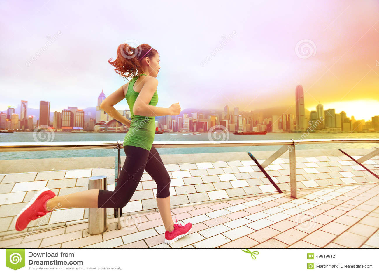 Stads- löparekvinna som joggar i Hong Kong på solnedgången