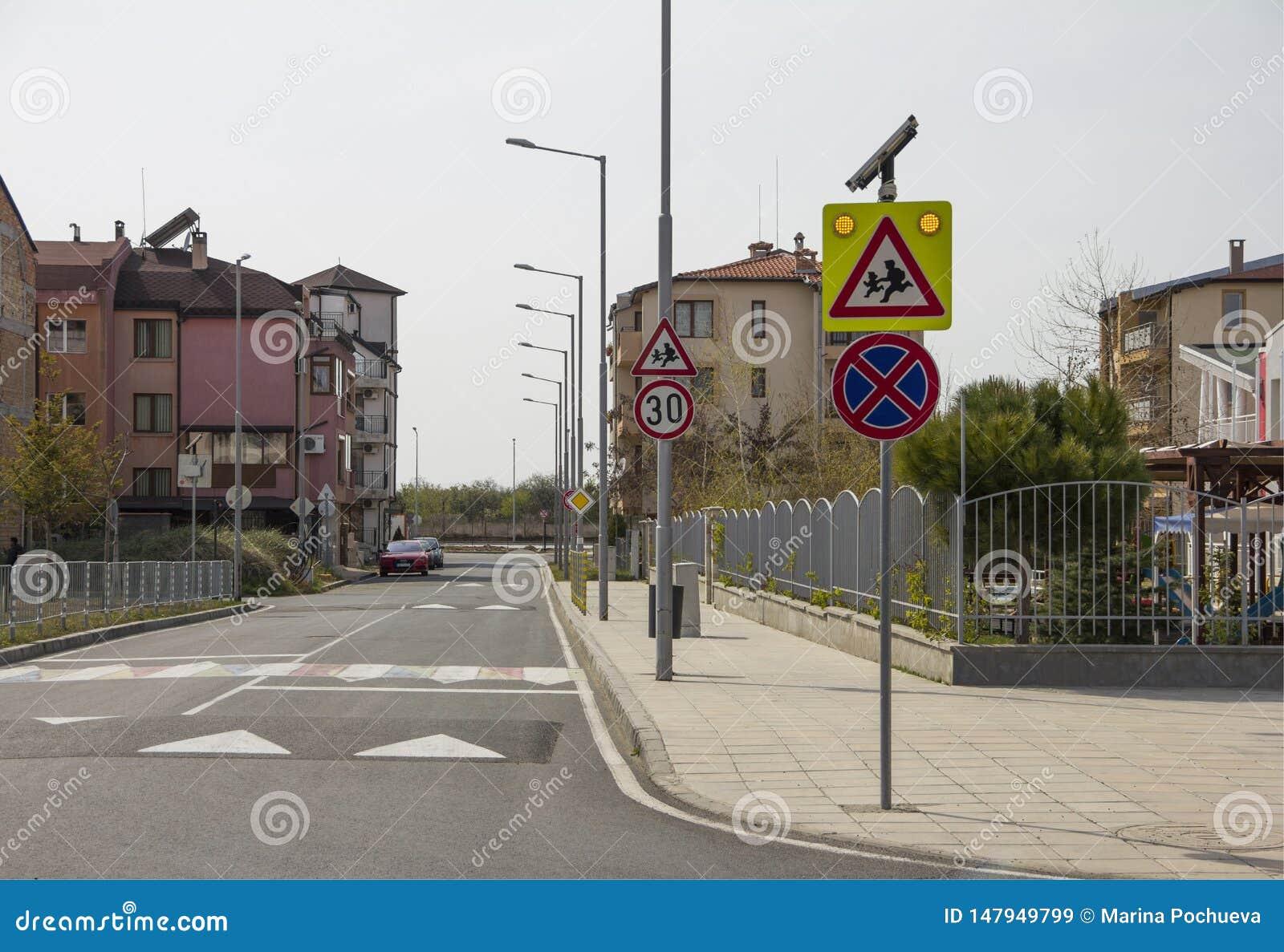 Stadsgata med en övergångsställe, en hastighetsbula och ett varningstecken 'barn 'nära ett härligt dagis