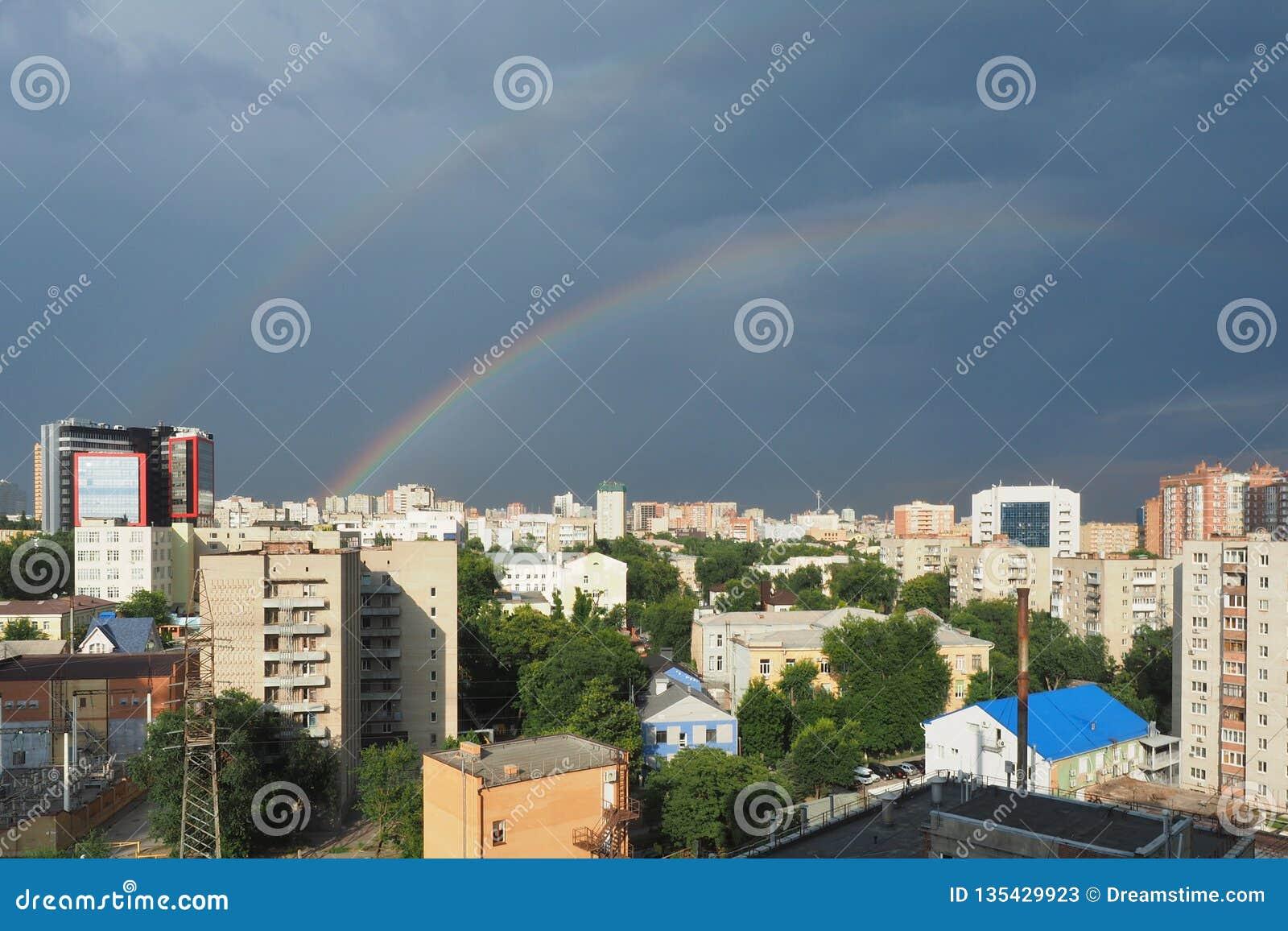 Stadsgebouwen op de achtergrond van zwarte hemel met regenboog