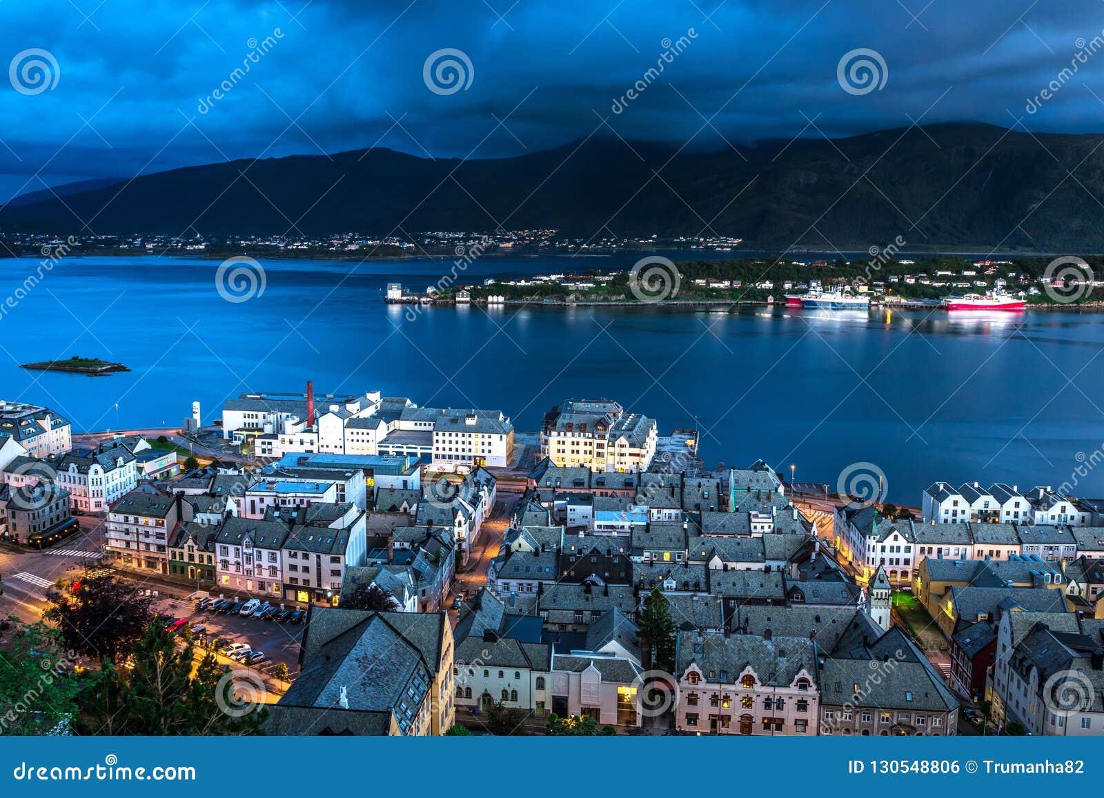 Stadsplats med flyg- sikt av den Alesund hamnen, fjärden och berg under blå timme