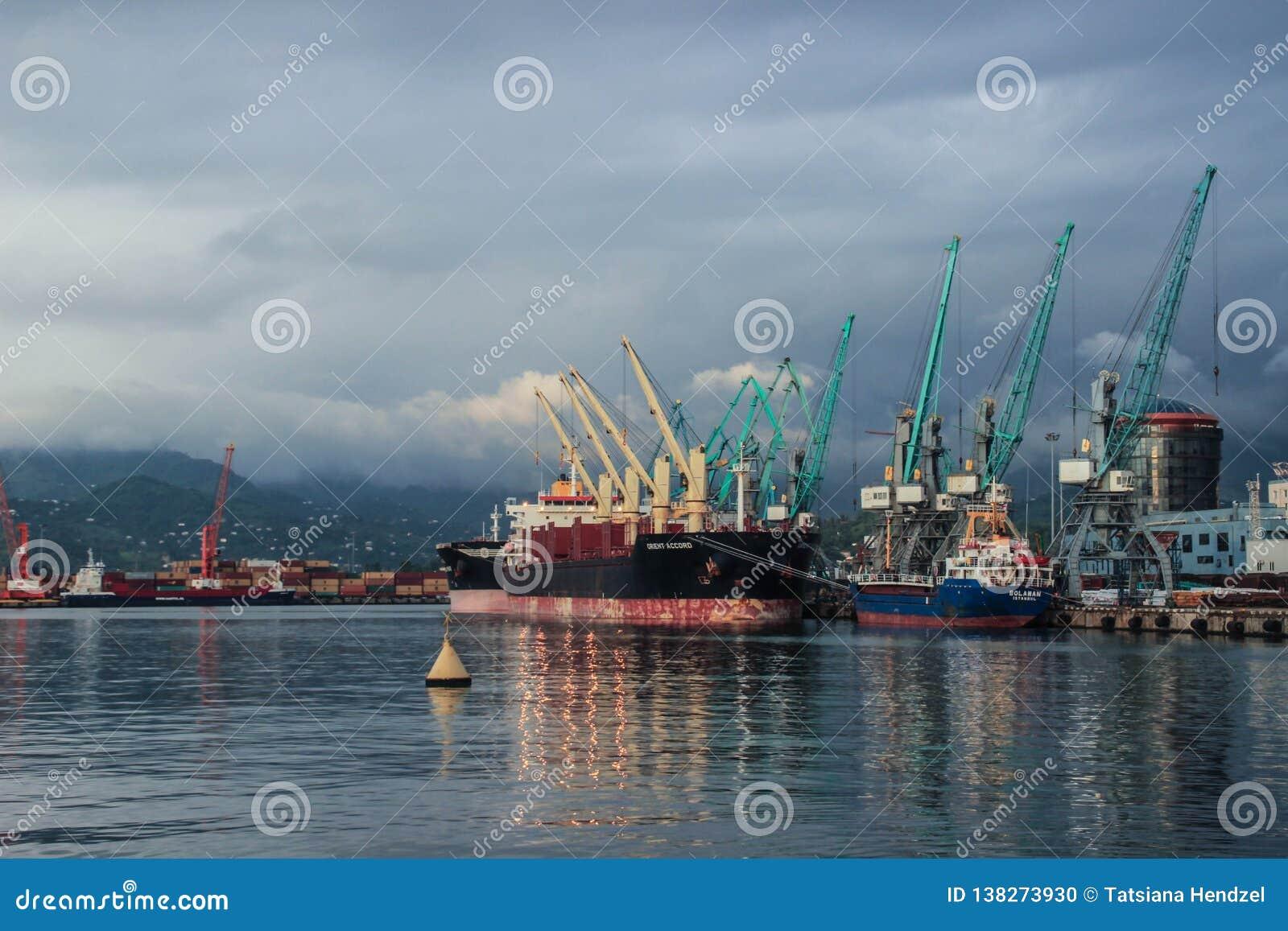 Stadsport med lastfartyg, pråm och kranar på solnedgången