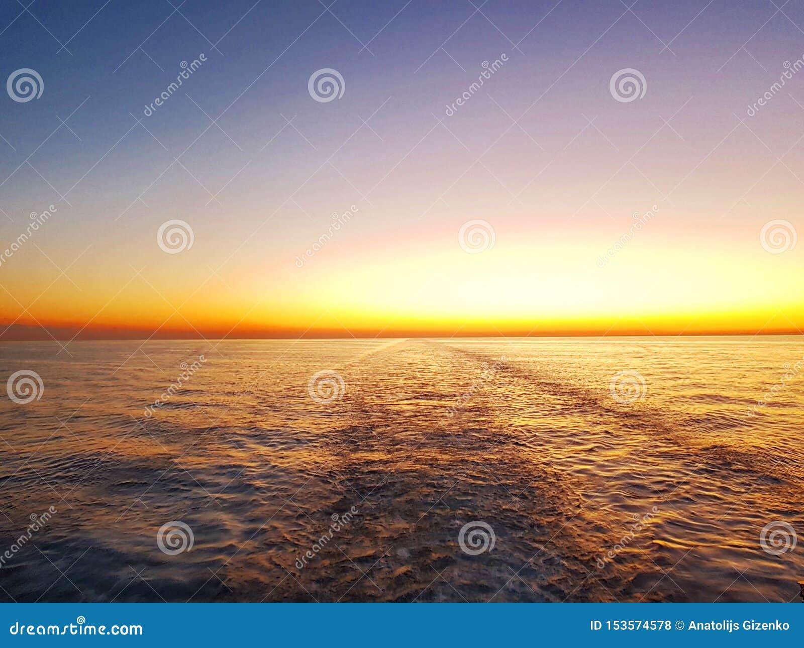 Stadssikts- och solnedgånghimmel Fantasihimmel Solnedgång på bakgrunden av en stråle av vatten från propellern av ett rörande ske