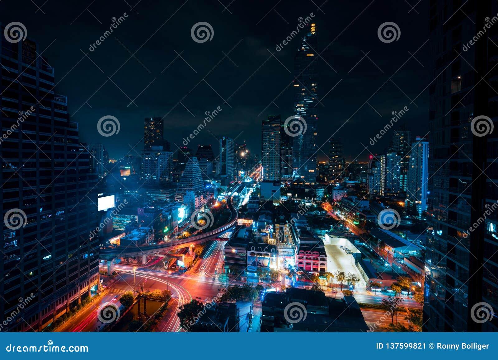 Stadtbild berühmten Maha Nakhon Towers in Bangkok, Thailand Helle Spuren in den Straßen von den Autos Bewölkter Himmel hinter