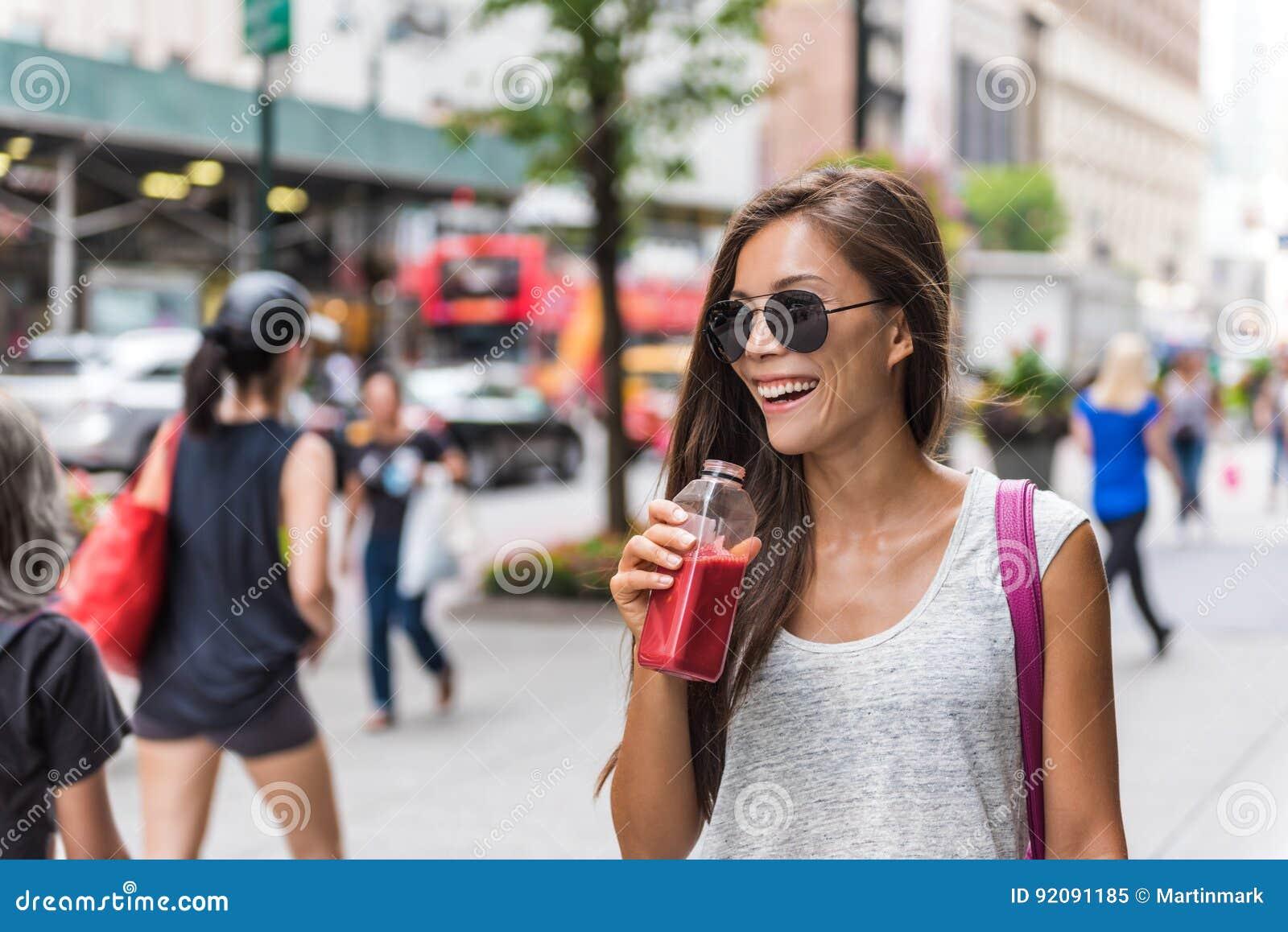 Stadtlebensstilfrau, die gesunden Fruchtsaft trinkt