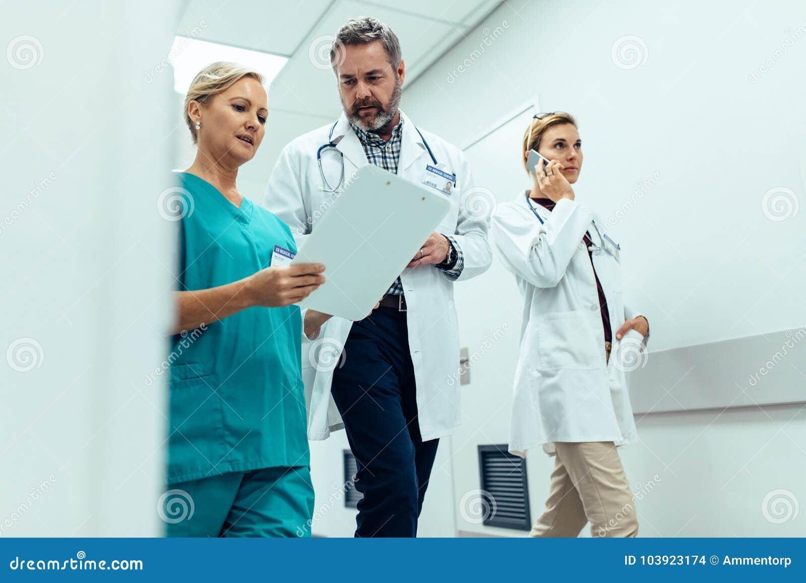 Staff ospedaliero occupato che discute nel corridoio dell ospedale