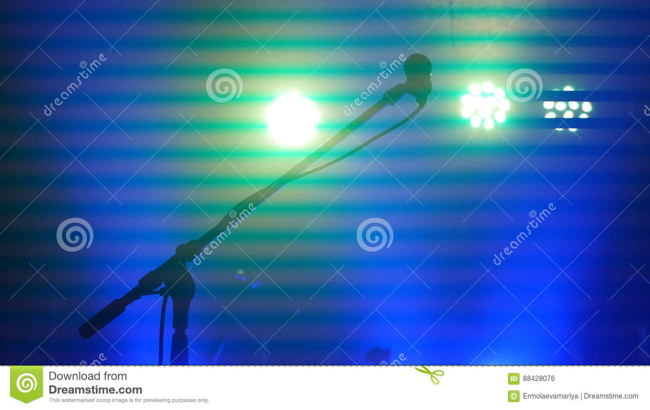 Stage lighting, equipment, beam and microphone stand in a night club