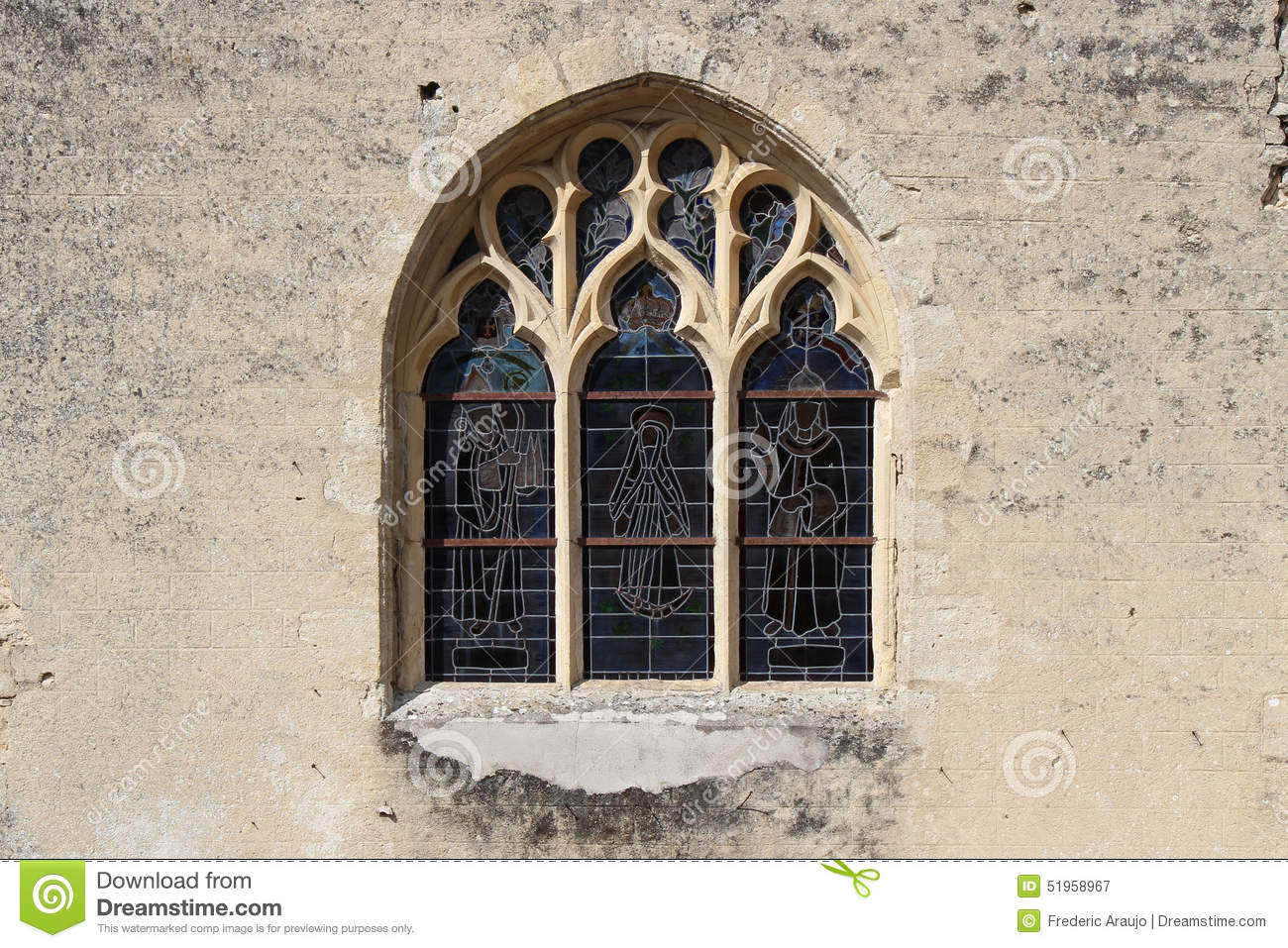 Stained-glass windows decorate the facade of a church in Occagnes (France)