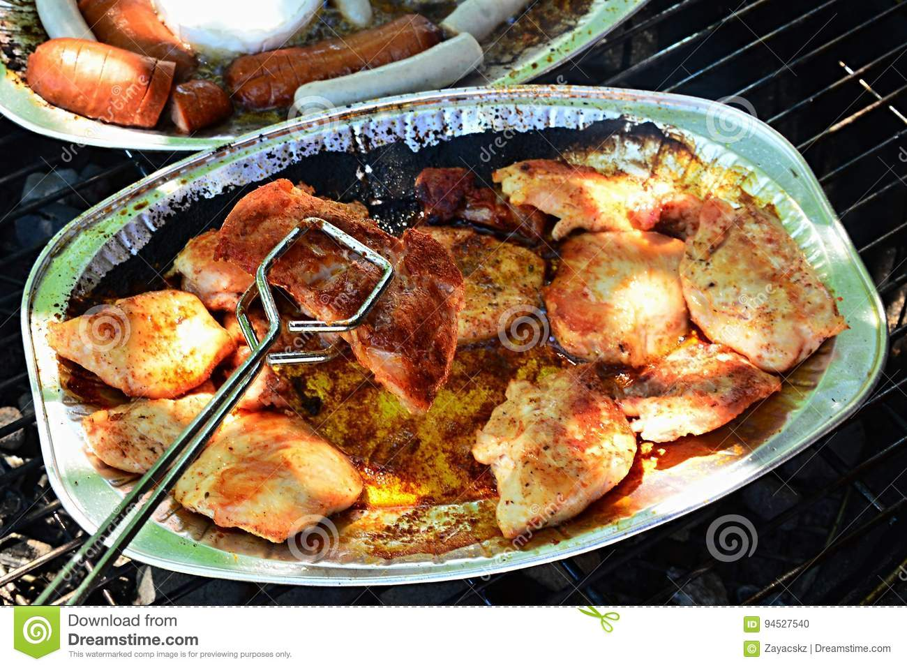 Stainless steel barbecue tongs holding crunchy grilled chicken breast above alluminium plate, sausage and camembert plate in backg