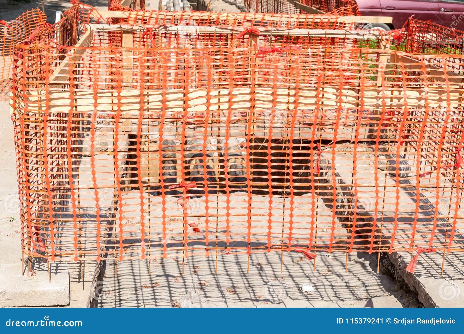 Staket för säkerhetsnät för konstruktionsplats orange som barriär över diket på gatautgrävningen