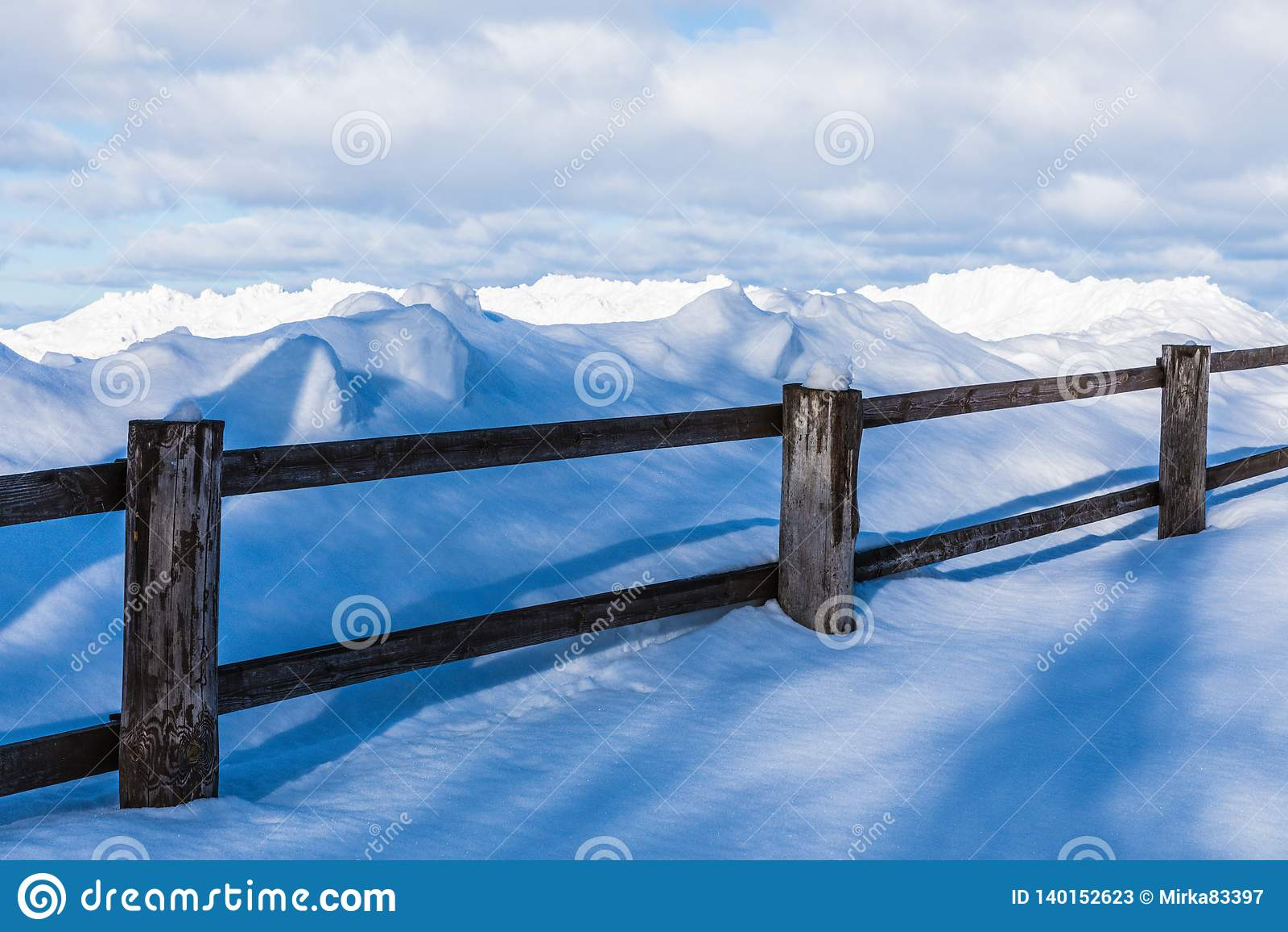 Staketet eller häcken och högarna av insnöat bygden eller i byn i den kalla vinterdagen
