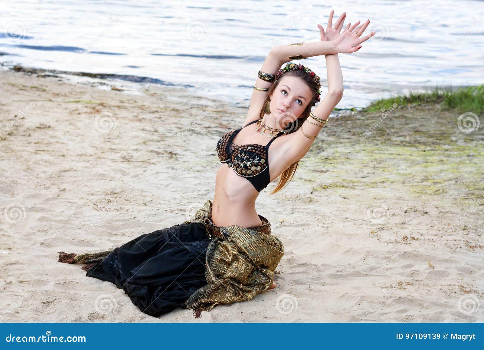 Stam- amerikansk stildansare för ung kvinna Flickadans och posera på dräkten för magdans för strandsand den bärande ethnic