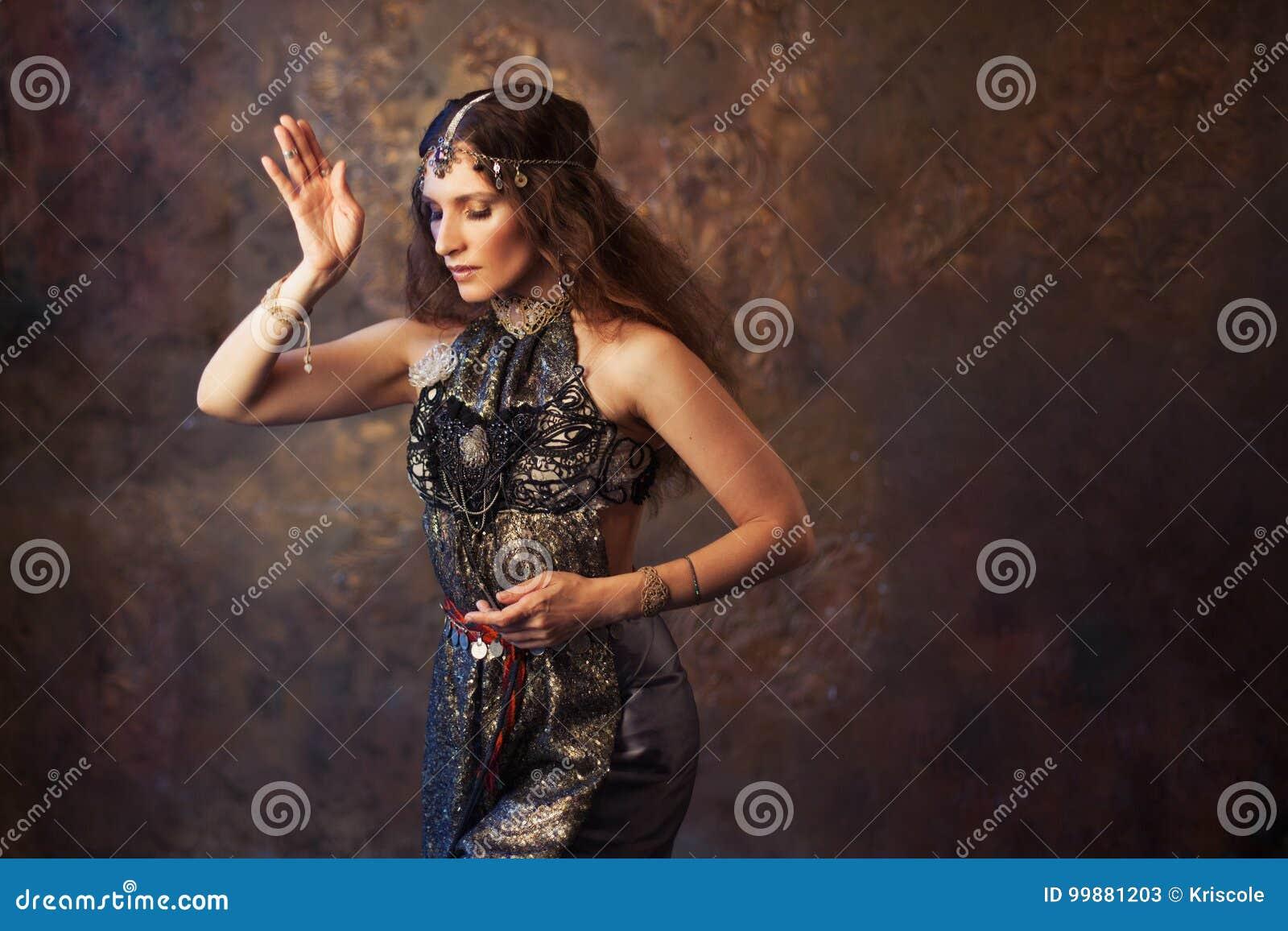 Stam- dansare, härlig kvinna i den etniska stilen på en texturerad bakgrund