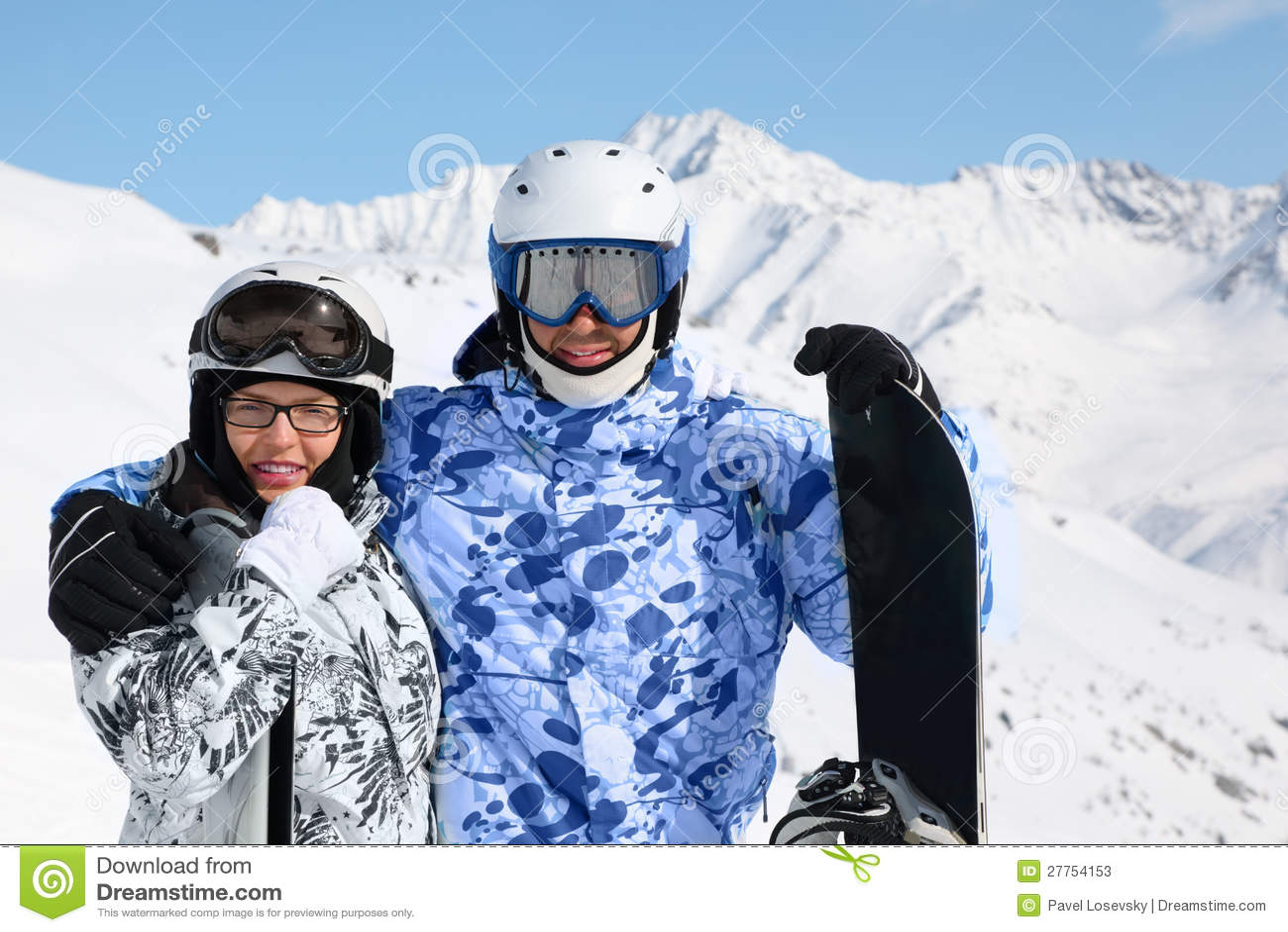 Stand de couples avec le snowboard et les skis