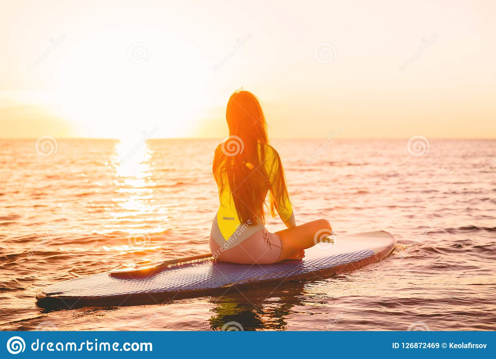Stand up paddle boarding on a quiet sea with sunset colors. Woman meditation on sup board