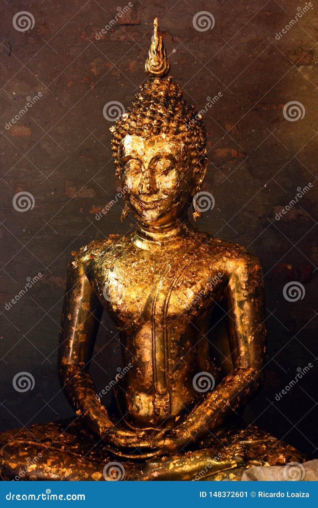 Standbeeld van Boedha behandelde met het aanbieden van gouden phra van bladerenwai bij Wat Yai Chai Mongkhon-tempel in Ayutthaya,