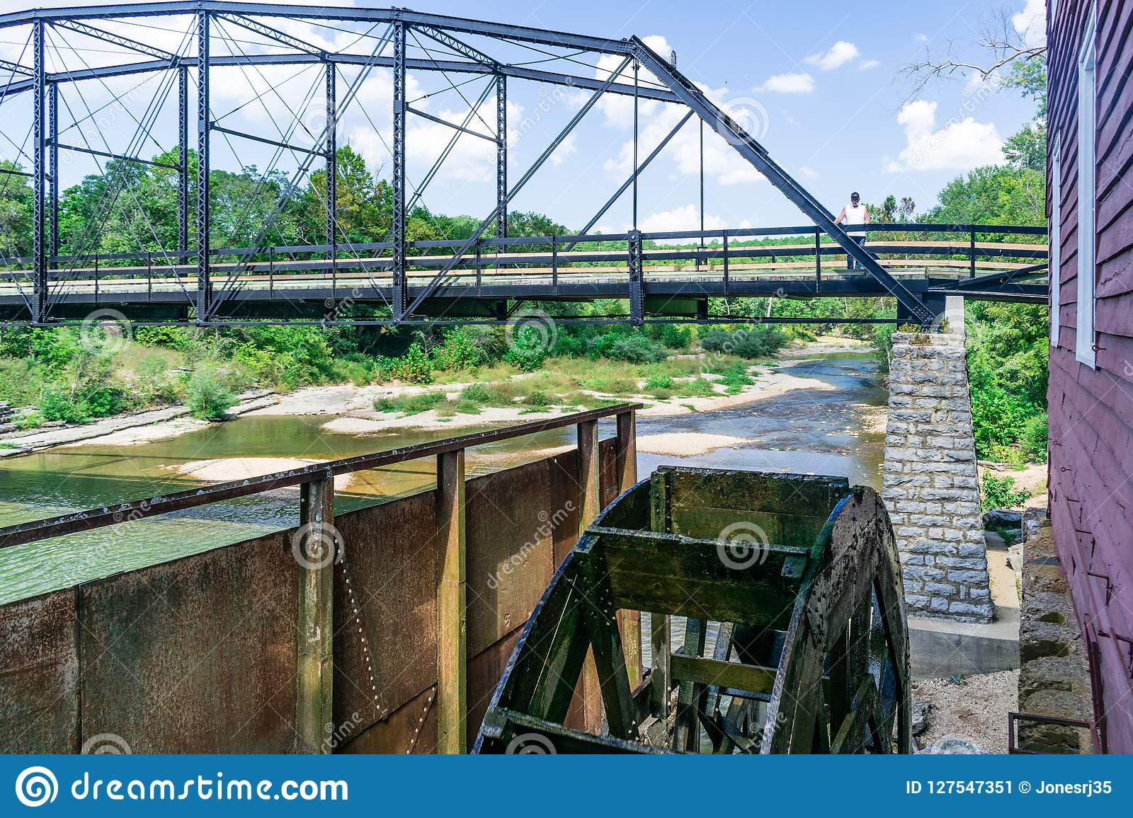 Standing on the historic War Eagle Bridge in Rogers, Arkansas one can see the working water wheel powered by the War Eagle River