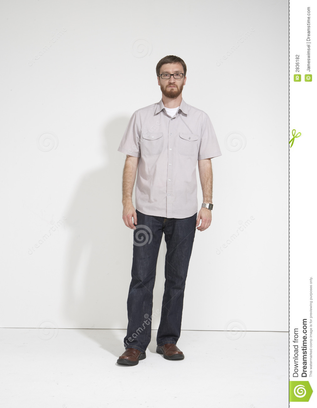 Bearded man against a white wall standing straight and looking ...