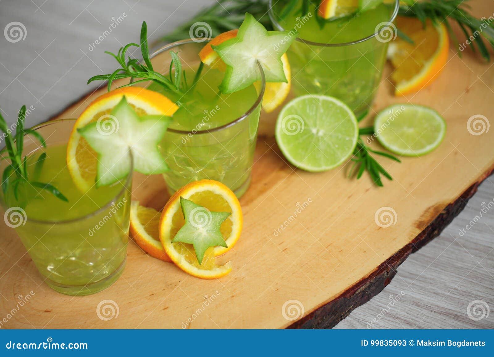 Standink vert de trois cocktails sur le bois, décoré de l orange, du carambolier, de la chaux et du romarin Préparez pour party
