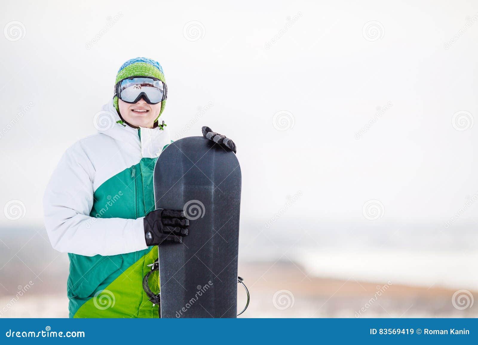 Standng de jeune homme sur la neige avec le surf des neiges