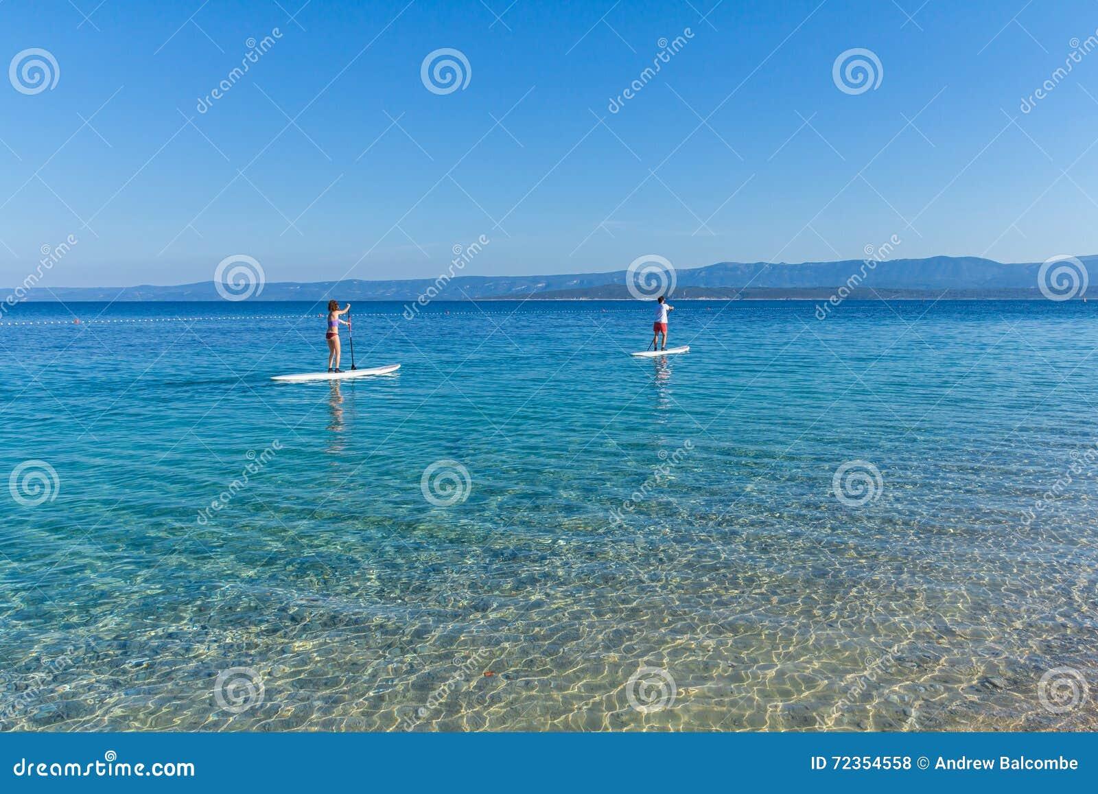 Standup Paddelinternatsschüler an Zlatni-Ratte setzen, Kroatien auf den Strand