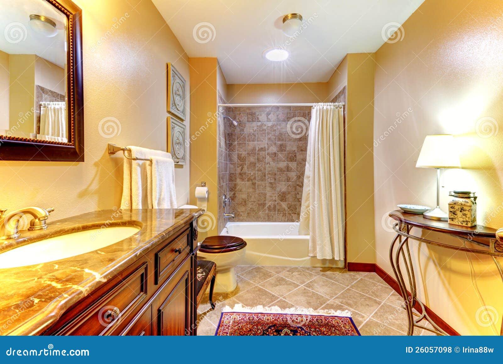 Stanza da bagno dorata con le mattonelle marroni fotografia stock