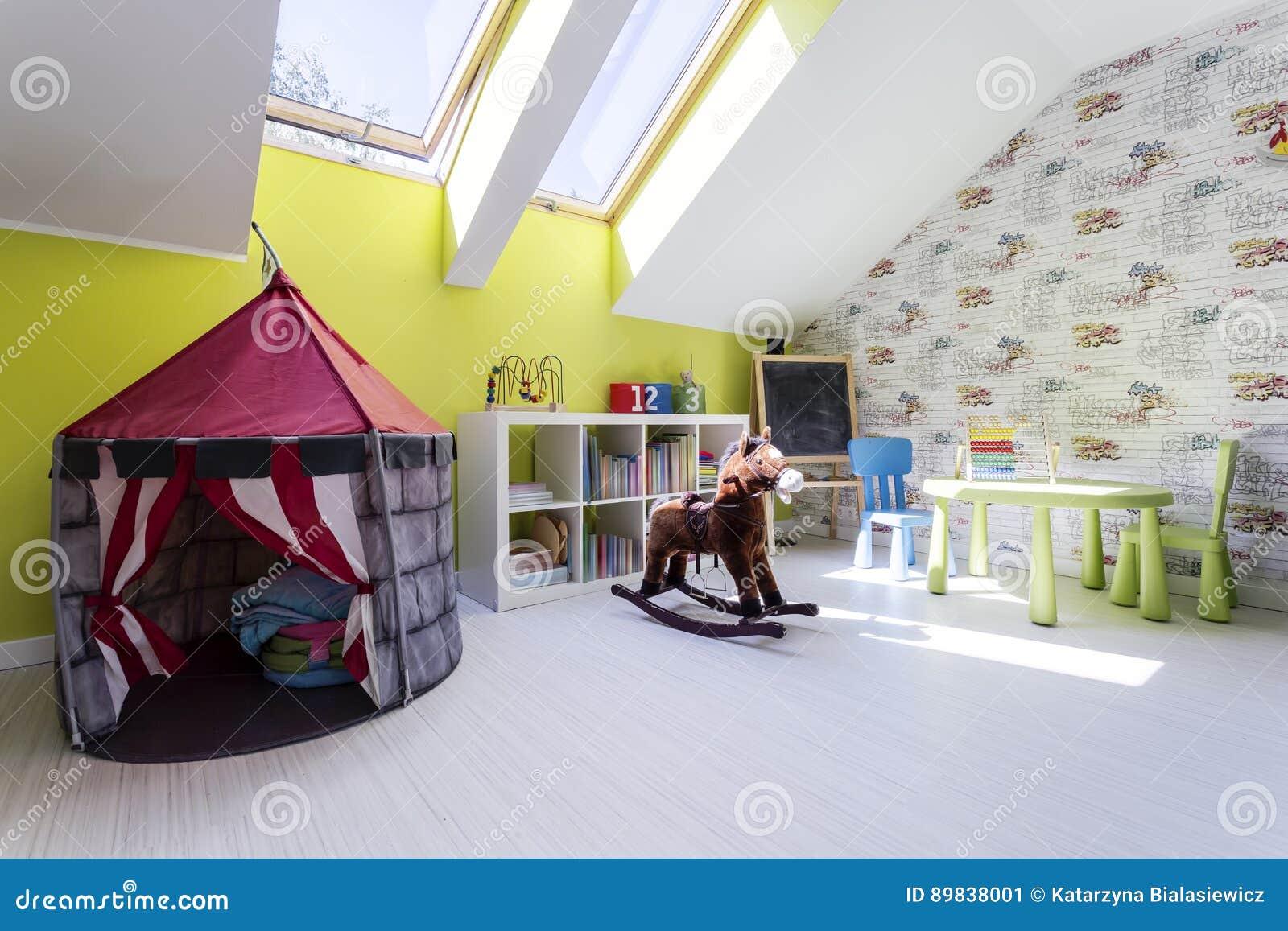 Stanza dei bambini con la tenda del gioco e un cavallo a dondolo