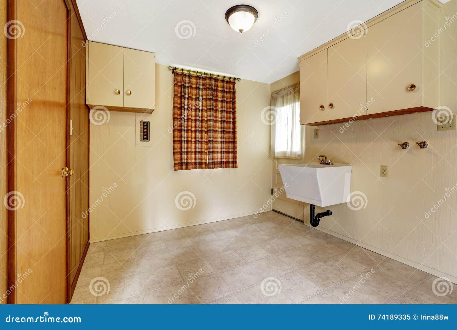 Stanza di lavanderia con le pareti e la pavimentazione in piastrelle beige ammobiliato di gabinetti e di guardaroba incorporato