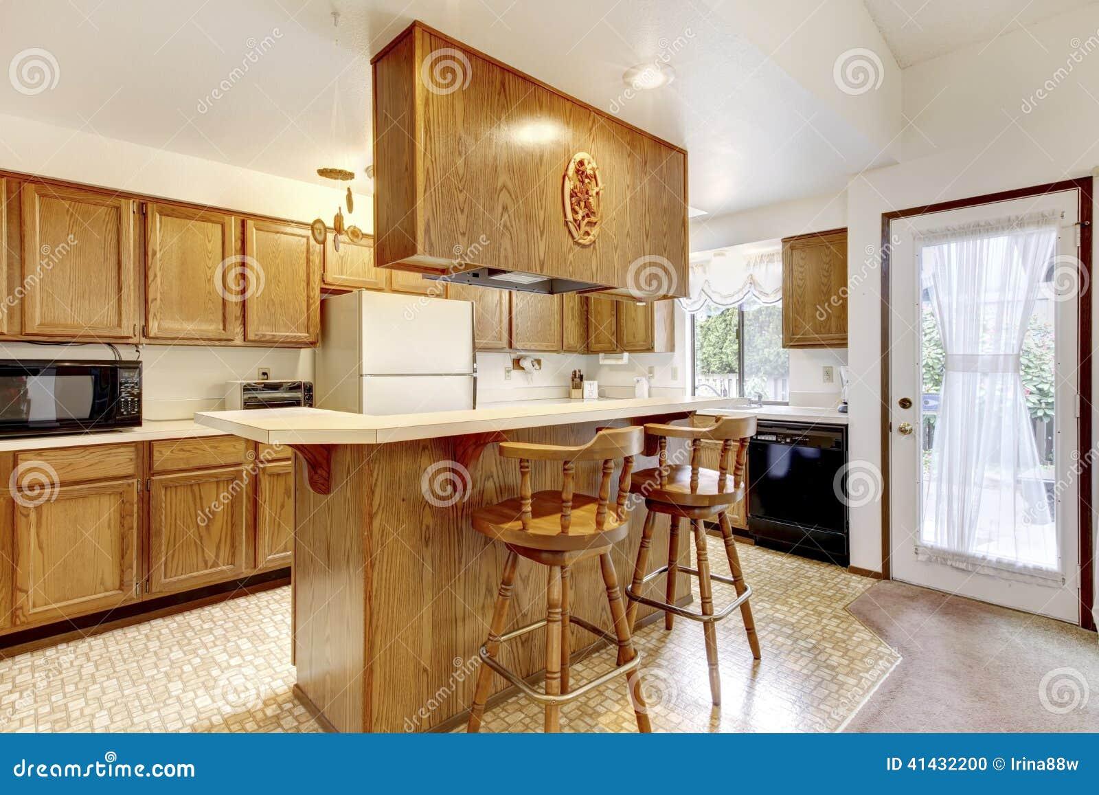 Stanza luminosa della cucina con gli sgabelli da bar rustici