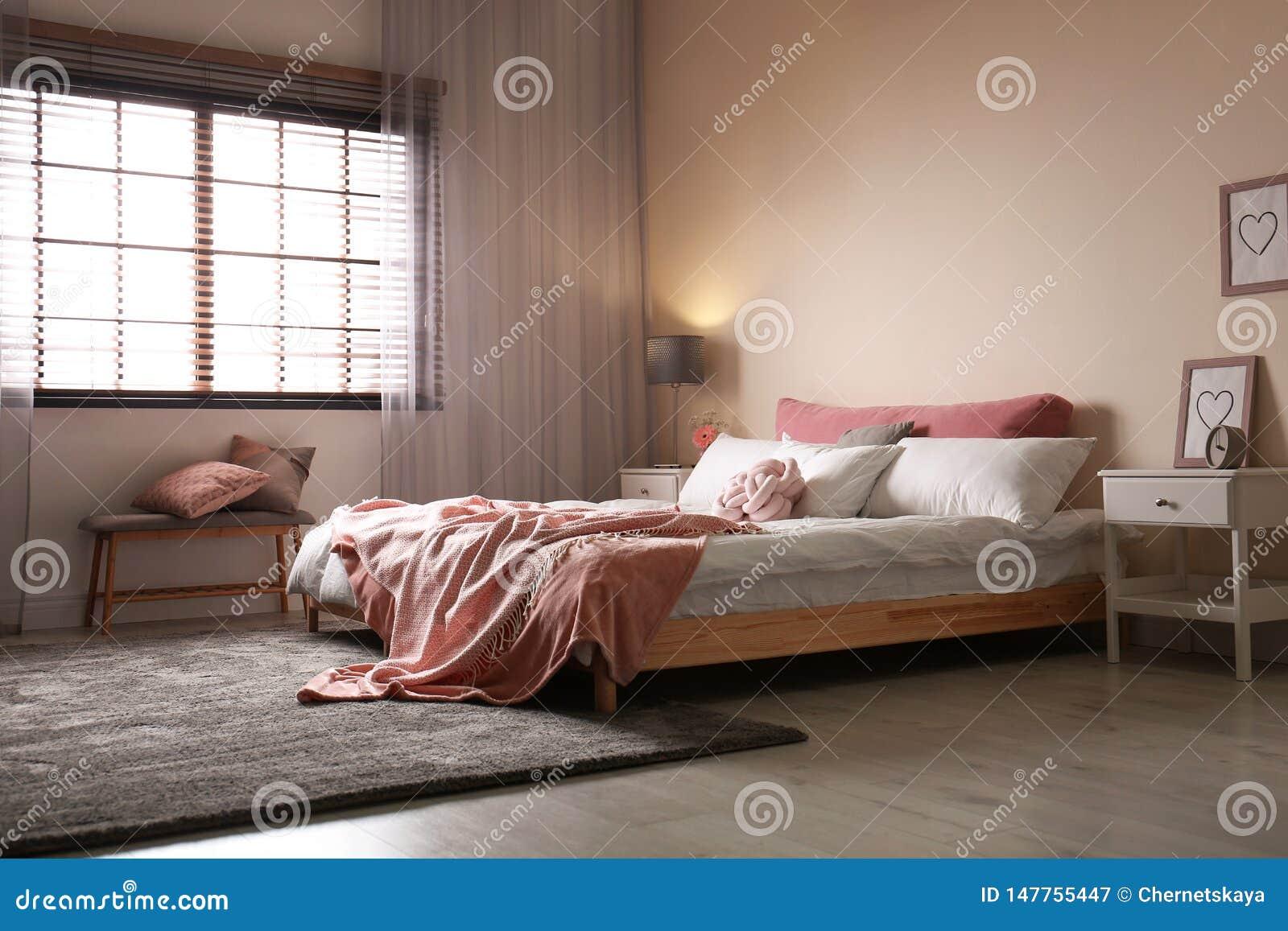Stanza moderna interna con i ciechi di finestra e del letto matrimoniale