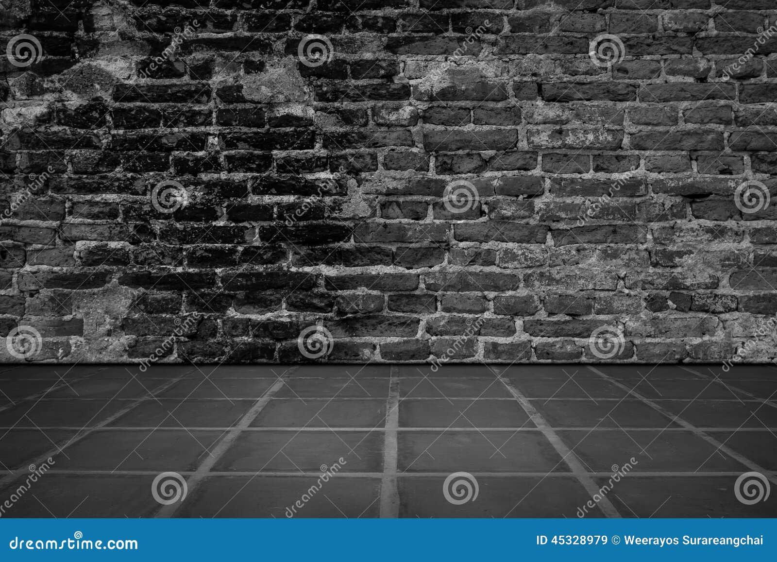 Stanza scura con il fondo del muro di mattoni e della pavimentazione