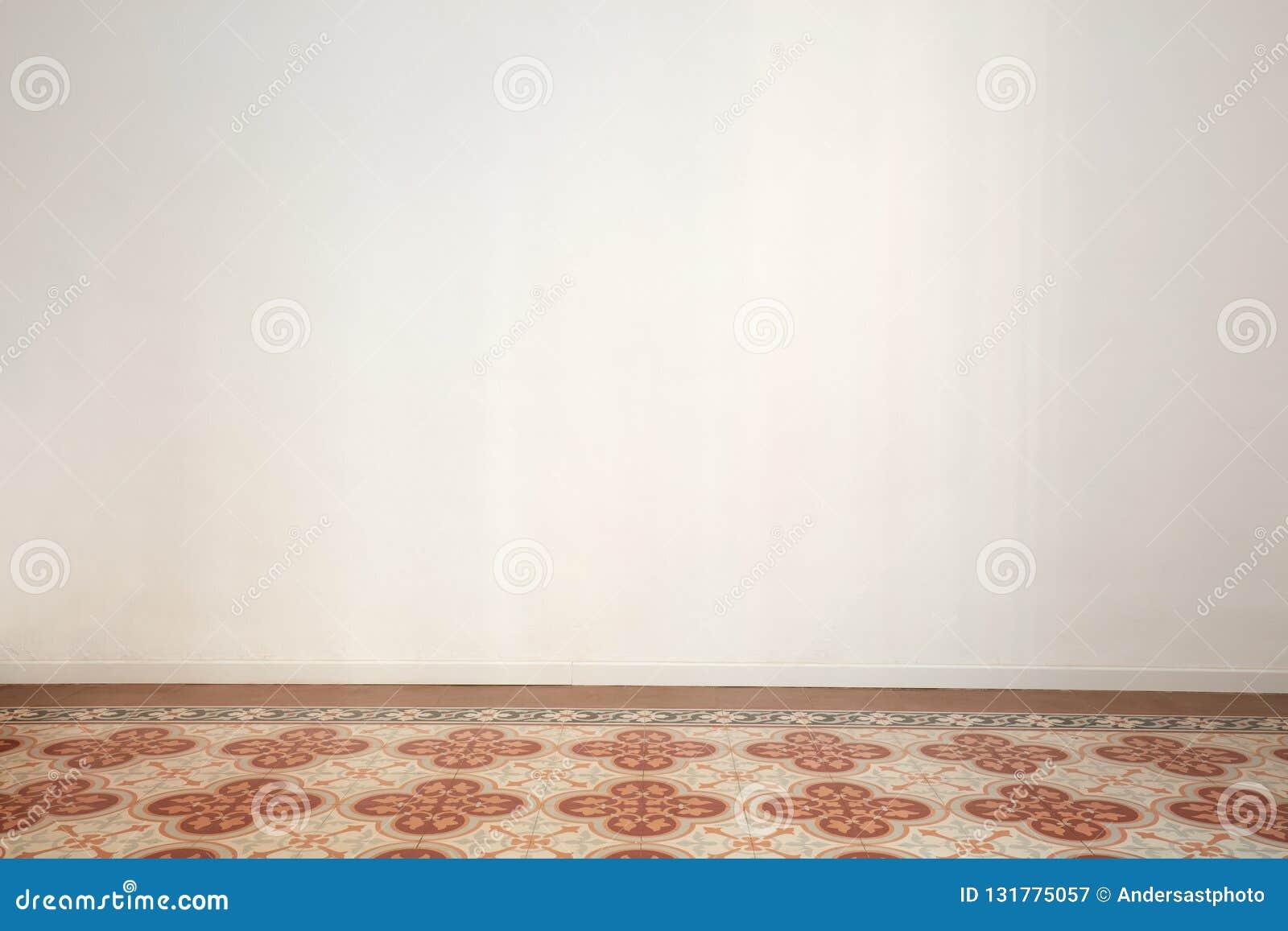 Stanza vuota con la parete bianca ed il pavimento non tappezzato antico in un appartamento rinnovato