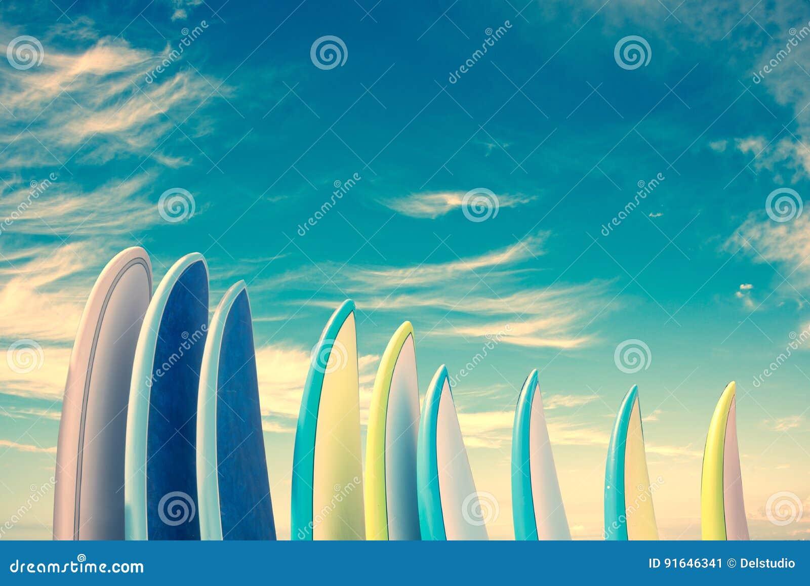 Stapel bunte Surfbretter auf Hintergrund des blauen Himmels mit Kopienraum, Retro- Weinlesefilter