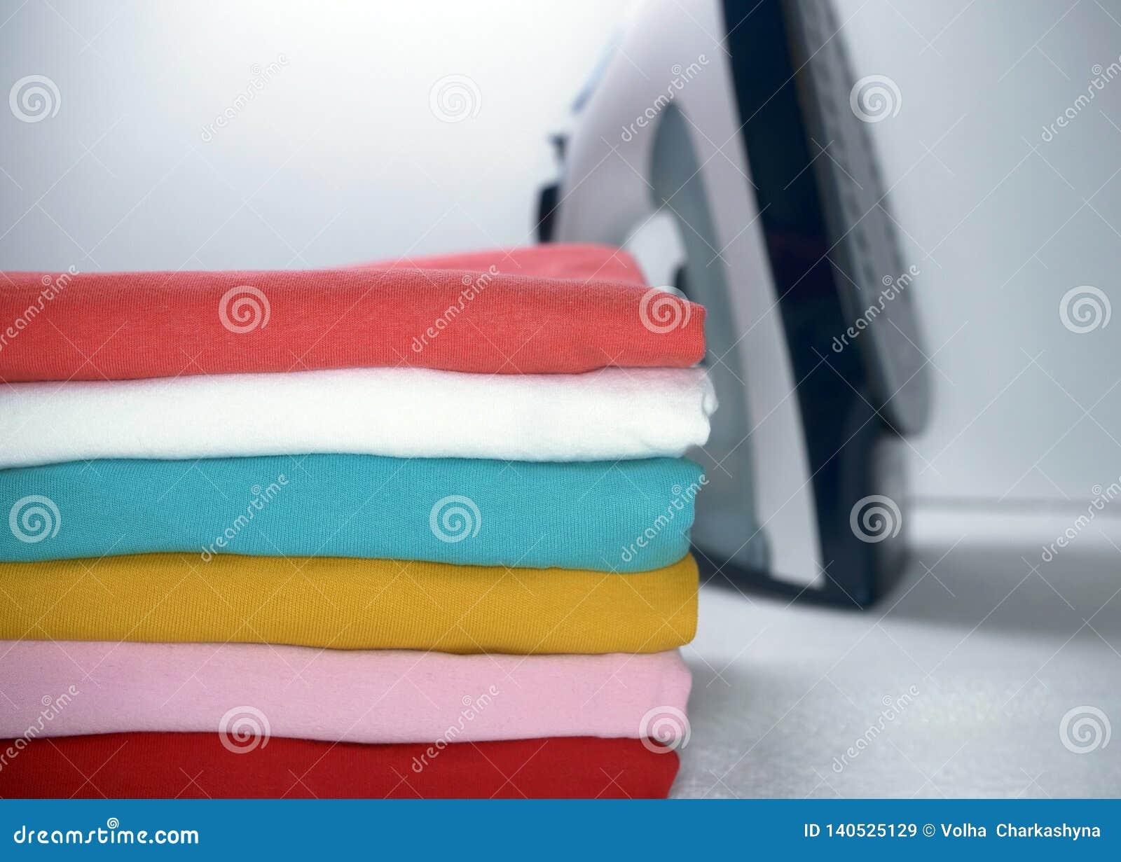 Stapel der gebügelten Kleidung und des Eisens auf weißem Hintergrund