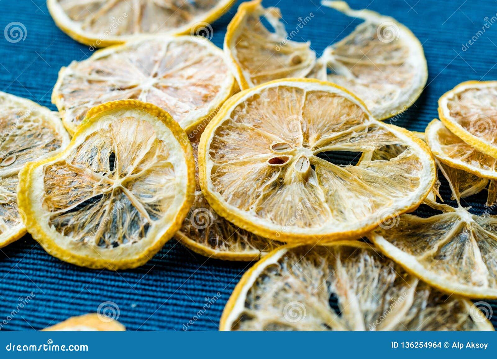 Stapel getrocknete Zitronen-Scheiben auf blauer Oberfläche/trockenes und geschnitten