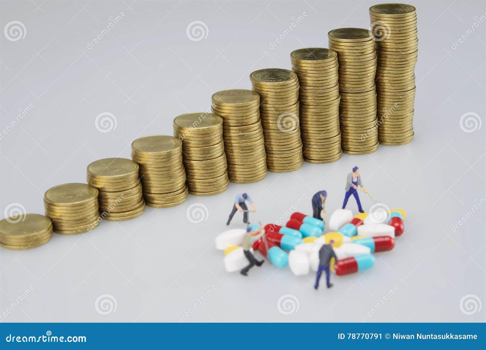Stapel Goldmünze und Miniaturleute mit Medizin