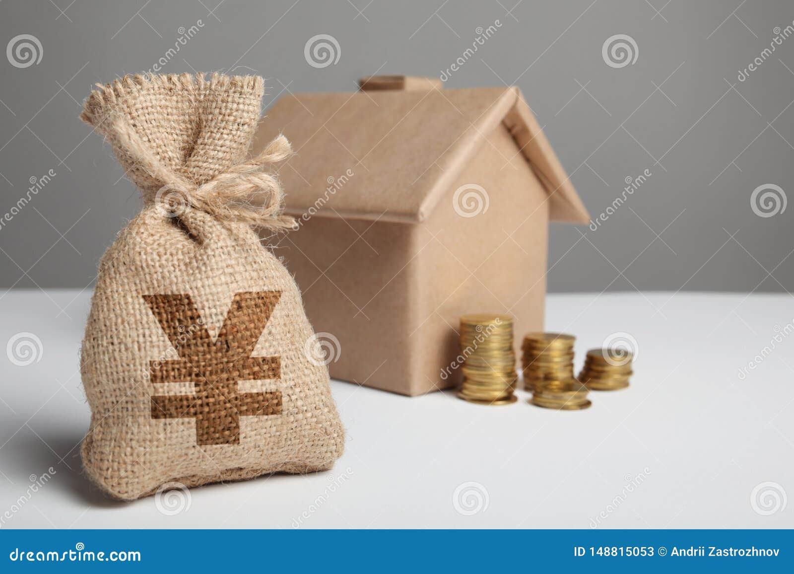Stapel gouden muntstukken en het cijfer van het bewerken van huis Zak met geld en yuansteken Investering in landgoedbezit Huishuu