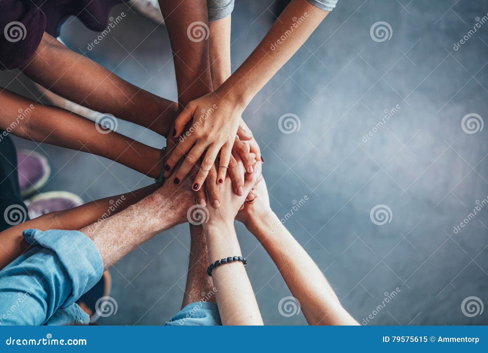 Stapel handen die eenheid en groepswerk tonen