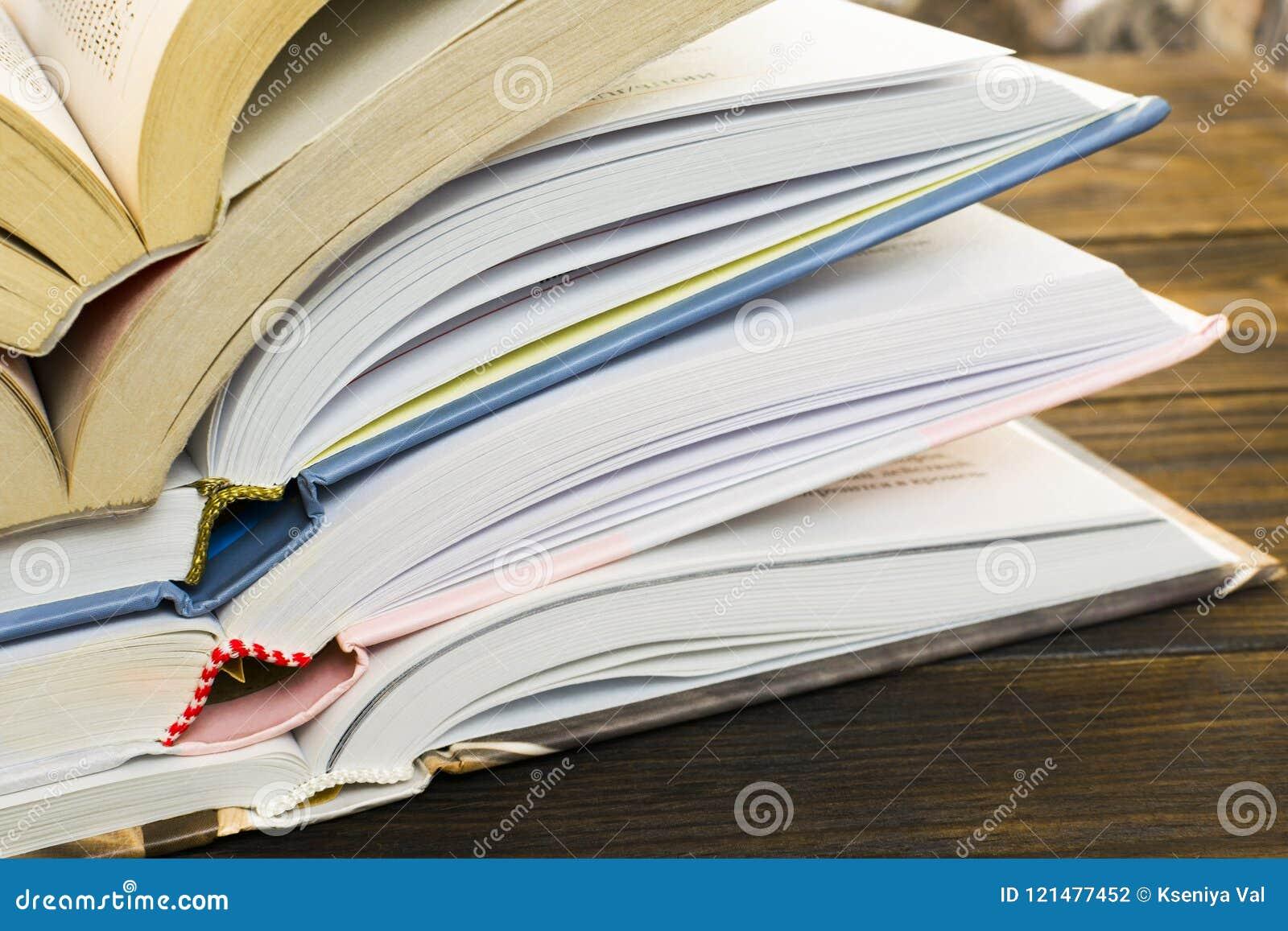 Stapel open boek met harde kaftboeken op een oude donkere bruine houten lijst Onderwijs