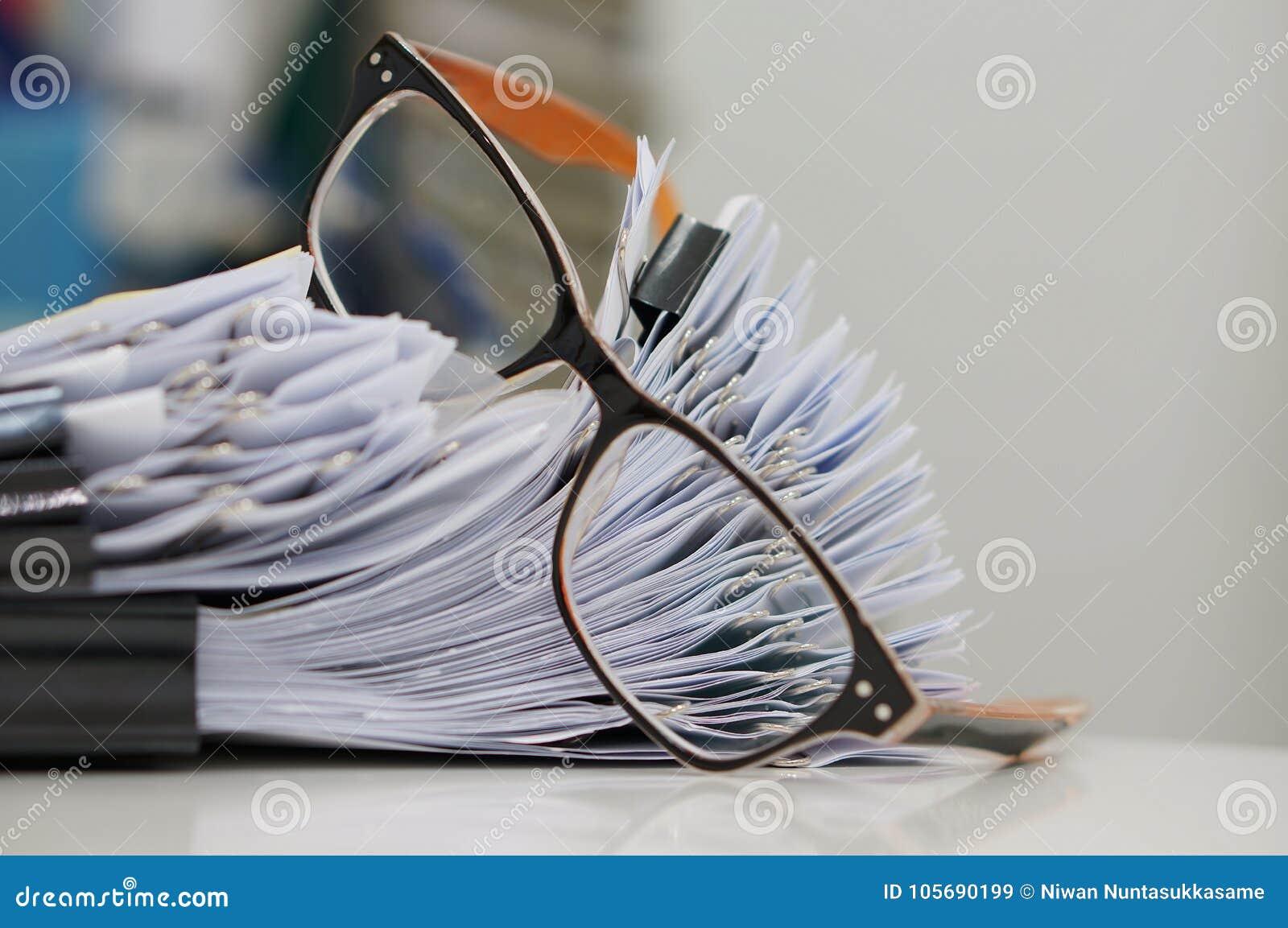 Stapel Papierarchive mit Clipn auf Schreibtisch für Bericht und Gläsern im Büro am Morgen