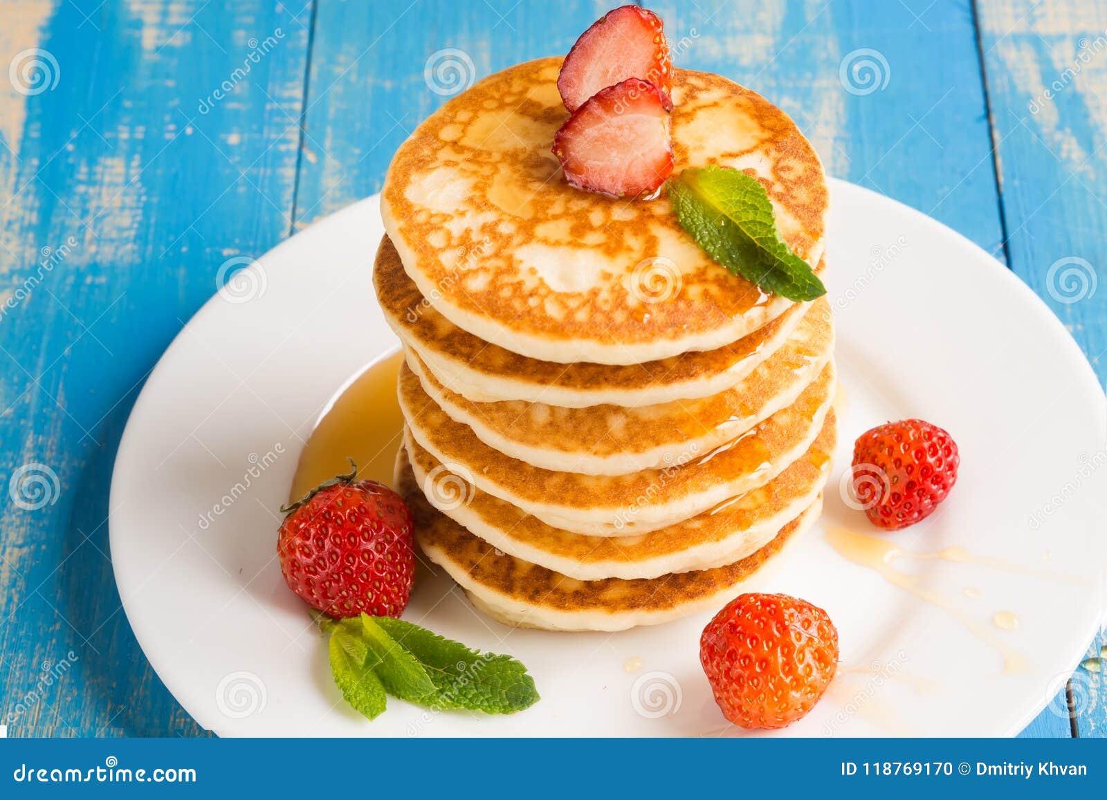 Stapel Pfannkuchenstückchen mit Erdbeeren und Honig auf einem pl
