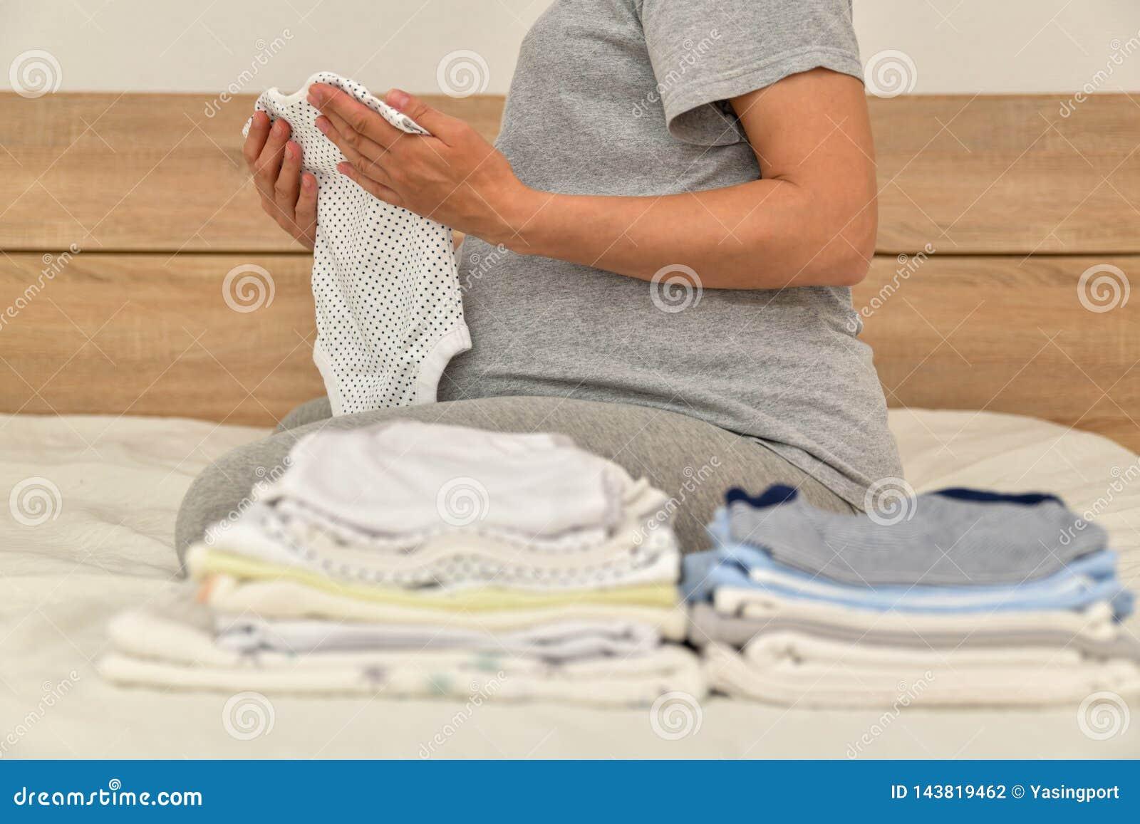 Stapel van babykleren en zwangere vrouw op een bed