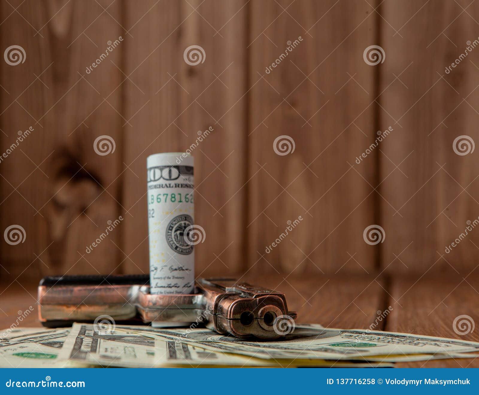 Stapel van Geld, drugsand een kanon op een houten lijst, concept over gevaar en bedreiging van de drug