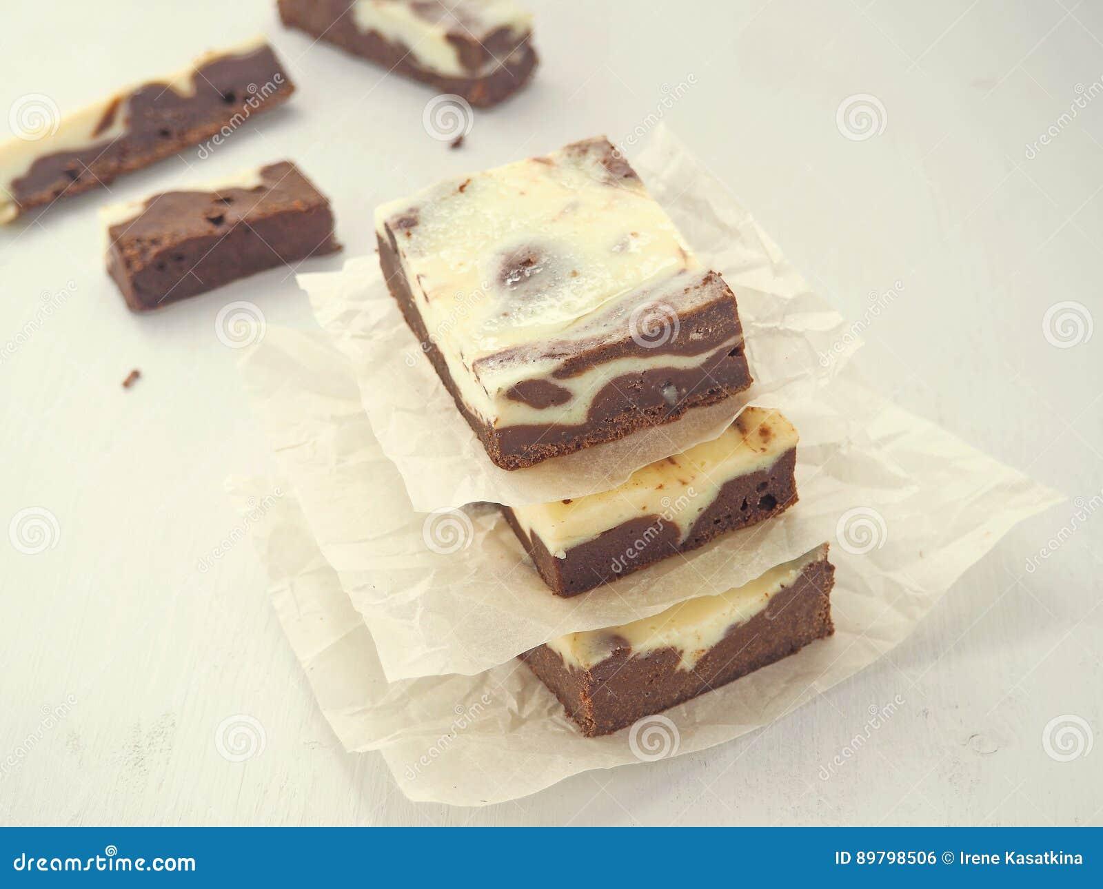 Stapel van marmeren chocolade drie brownies Eigengemaakt dessert op perkament Vierkante stukken van browniekaastaart